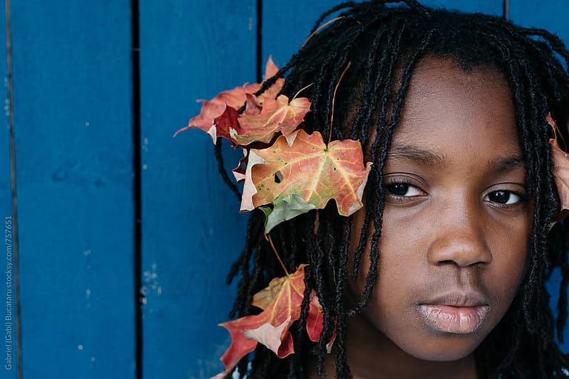 Black girl with autumn leaves in her hair by Gabriel (Gabi) Bucataru for Stocksy United