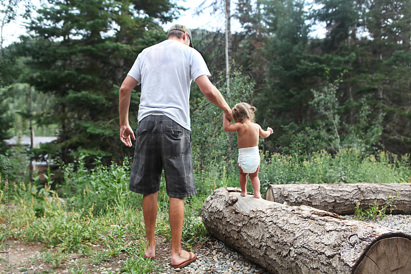 Father holding toddlers hand walking in forest by Dina Giangregorio for Stocksy United