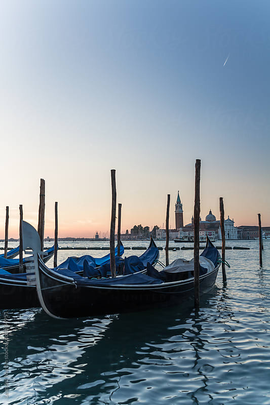 Venetian gondolas with the basilica san giorgio maggiore in the back. by Leander Nardin for Stocksy United