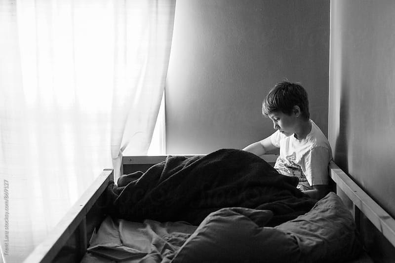Side view of boy reading at home during homeschool by Trent Lanz for Stocksy United