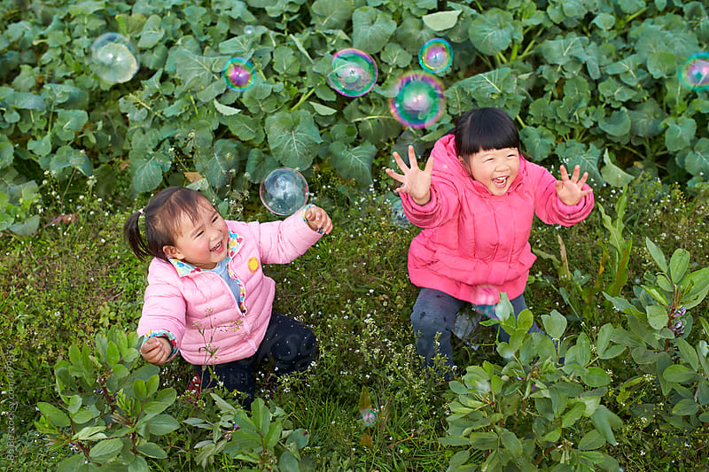 two happy little asian girls playing with soap bubble outdoor by Bo Bo for Stocksy United