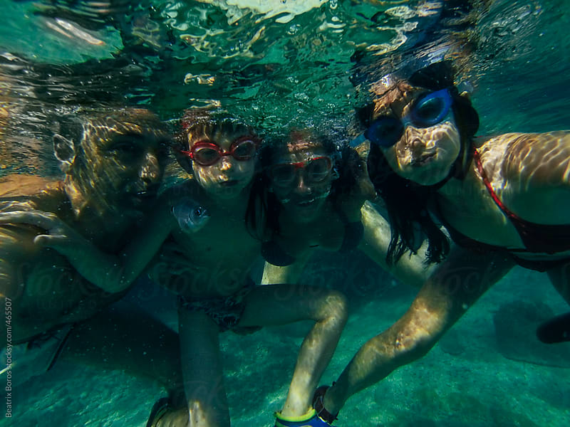 Family underwater selfie with a little fish by Beatrix Boros for Stocksy United