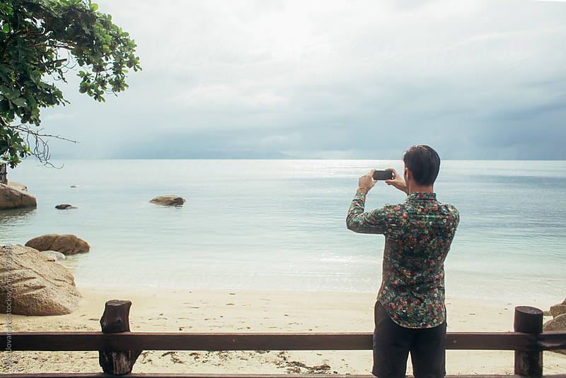 Landscape image of back side of young man taking a picture of beach and water by Jovo Jovanovic for Stocksy United