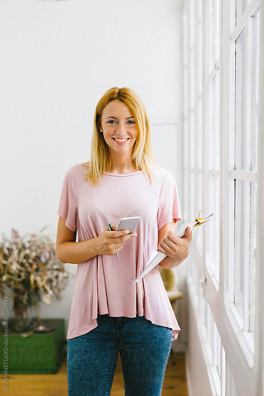 Entrepreneur woman using her smartphone at office. by BONNINSTUDIO for Stocksy United