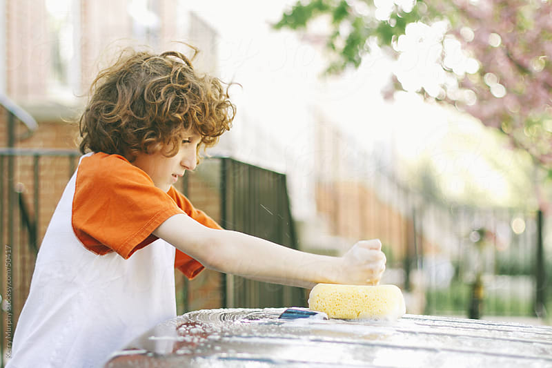 Curly haired boy washing car in summer by Kerry Murphy for Stocksy United