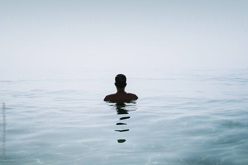 Back View of a Man Bathing in a Calm Sea by Victor Torres for Stocksy United