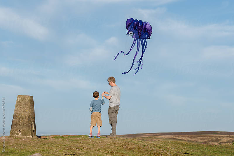 Dad helps his son fly a kite by Rebecca Spencer for Stocksy United