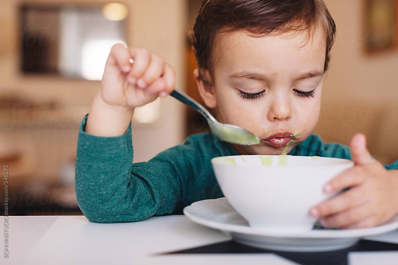 Young boy eating a vegetable puree soup for lunch at home. by BONNINSTUDIO for Stocksy United