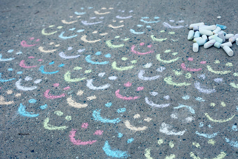 Tons of chalk smiles and one frown on the driveway by Carolyn Lagattuta for Stocksy United