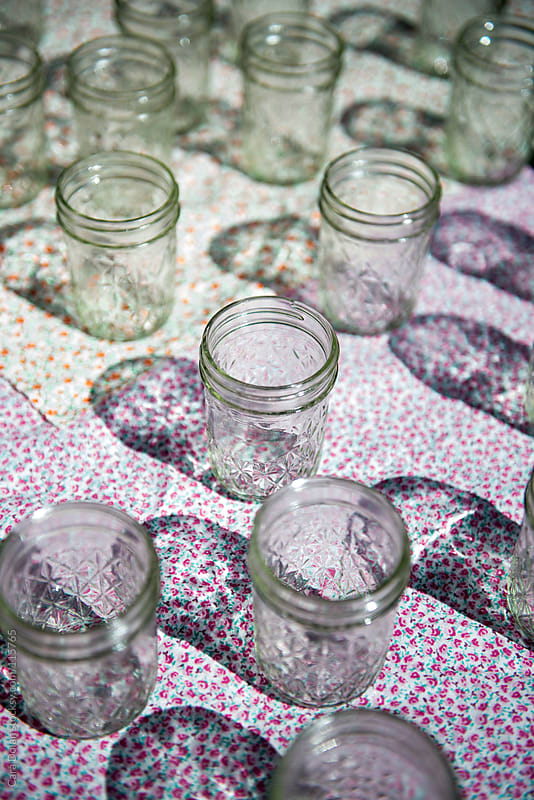 Glass jars on floral tablecloth by Cara Dolan for Stocksy United