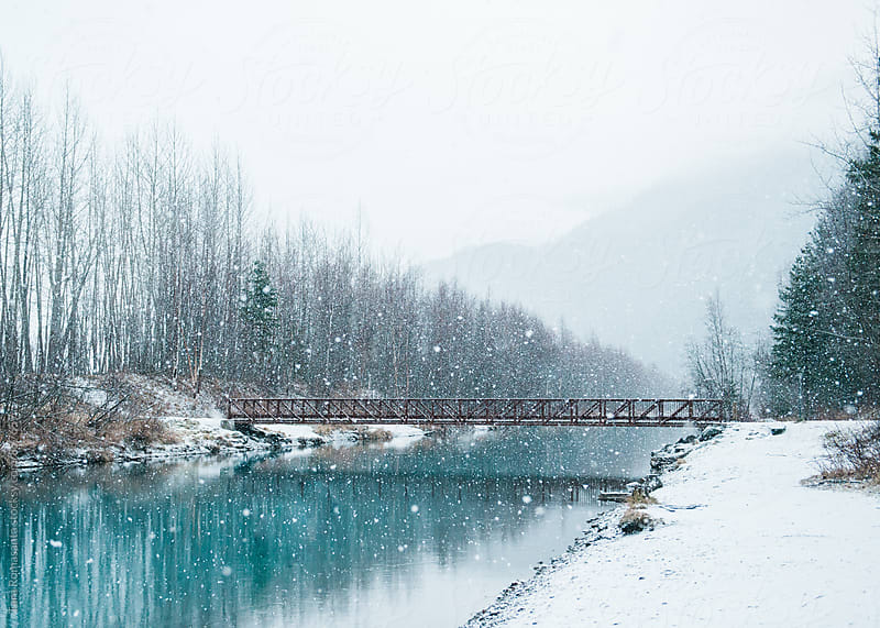 a pedestrian footbridge in falling snow by Tara Romasanta for Stocksy United