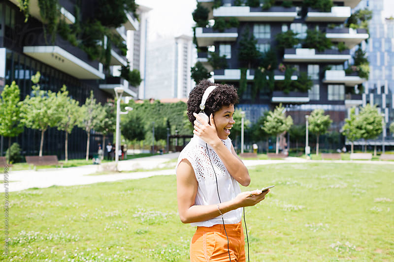 Young woman listening to music with headphones by michela ravasio for Stocksy United