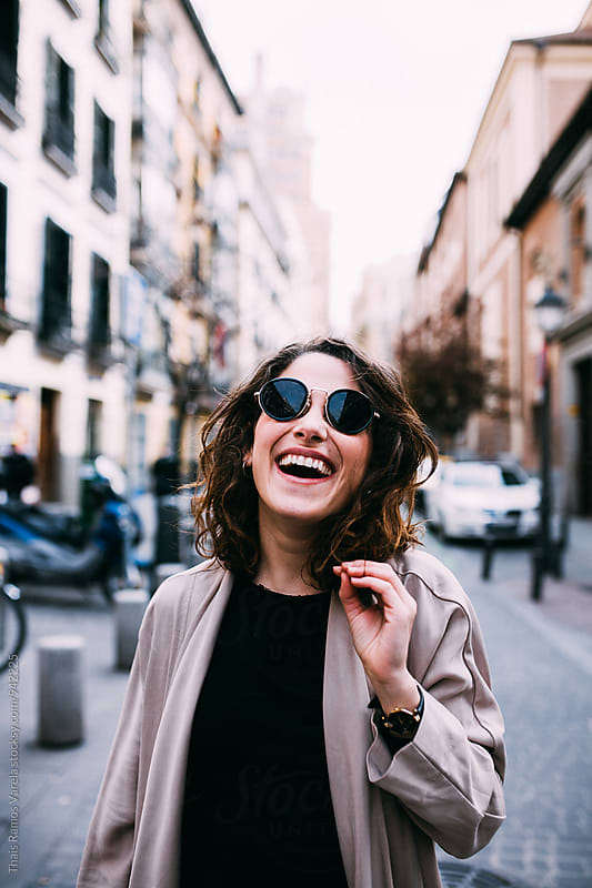 woman smiling in the street  by Thais Ramos Varela for Stocksy United