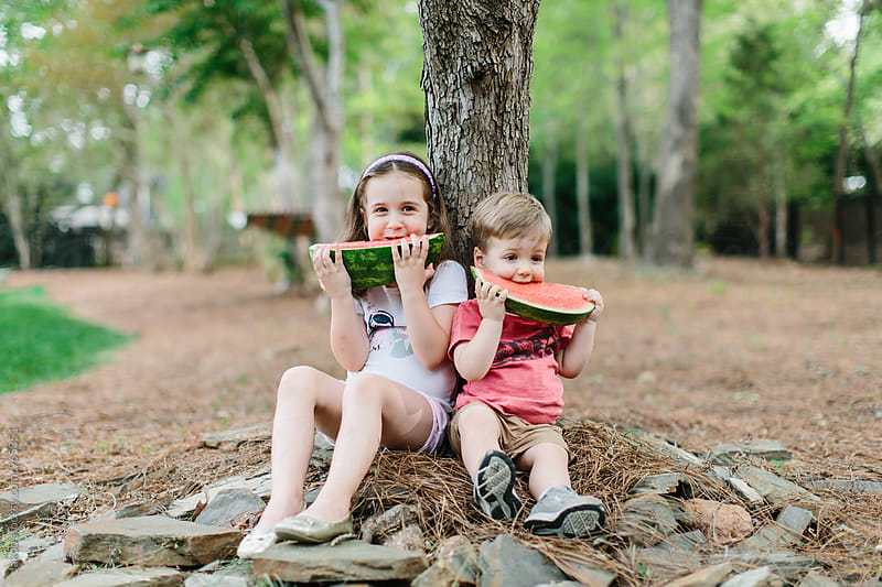 Cute young boy and girl eating watermelon under a tree by Jakob for Stocksy United