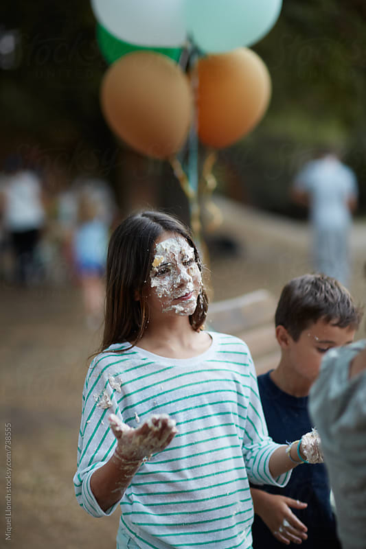 Young girl in a party with her face full of birthday cake by Miquel Llonch for Stocksy United