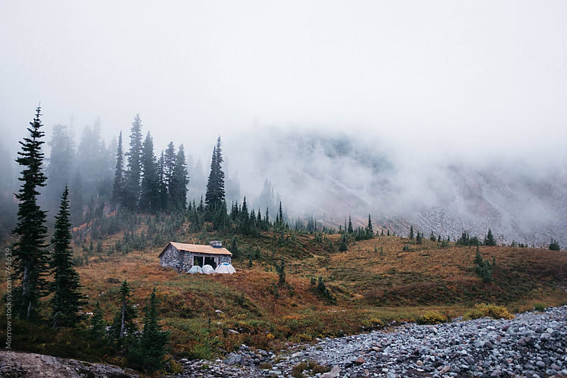 small cabin in high mountain forest with fog rolling in behind by Jesse Morrow for Stocksy United
