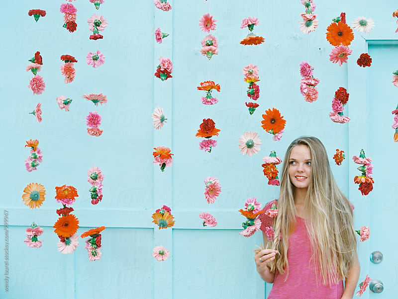blonde girl with flower wall with pink flowers by wendy laurel for Stocksy United