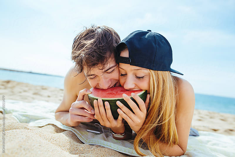 Teenage couple biting a watermelon on the beach. by BONNINSTUDIO for Stocksy United