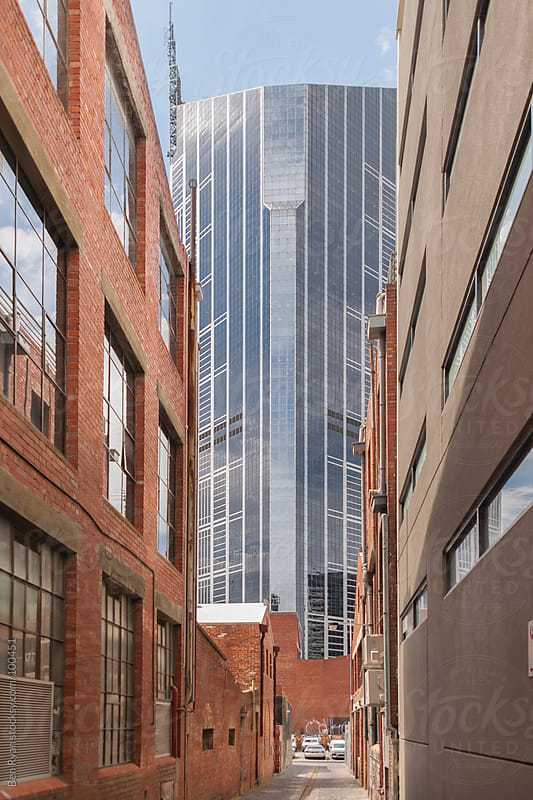 View down an historic alley to a modern skyscraper by Ben Ryan for Stocksy United