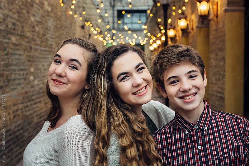Smiling teenage girls and boy in an alley by Gabriel (Gabi) Bucataru for Stocksy United