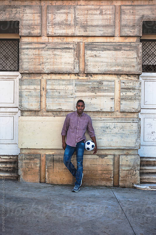 Portrait of a black man on the street with a soccer ball. by BONNINSTUDIO for Stocksy United