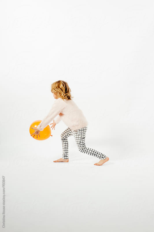 Young girl playing with an orange balloon against a white backdrop by Christina Rouse for Stocksy United