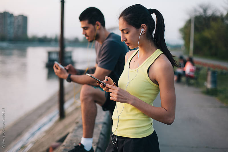 Couple browsing on their mobile phones after running  by VeaVea for Stocksy United