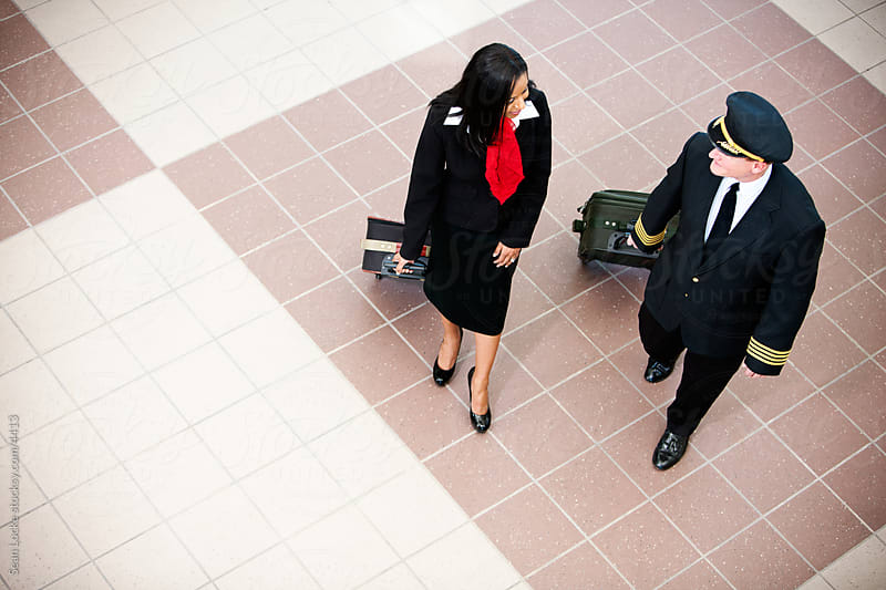 Airport: Captain and Flight Attendant Walking Through Airport by Sean Locke for Stocksy United