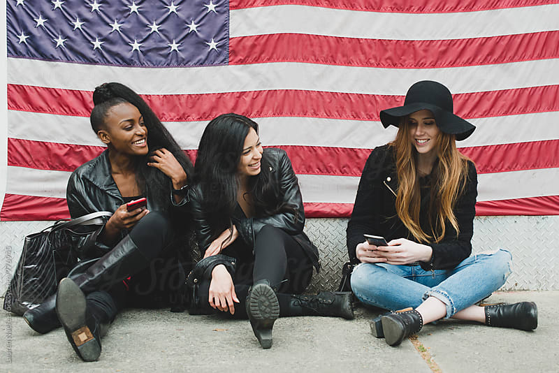Young women hanging out in street by American flag by Lauren Naefe for Stocksy United