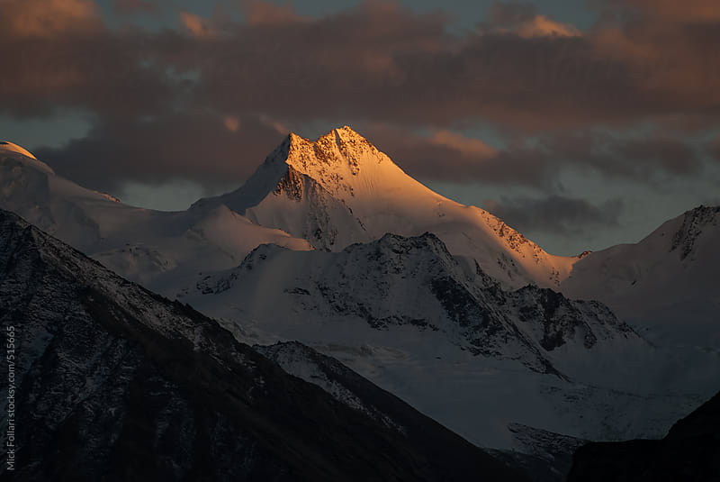 Dramatic sunset light on Himalayan peak. by Mick Follari for Stocksy United