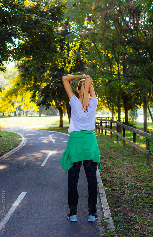 Young Woman Stretching Before Jogging by Mosuno for Stocksy United