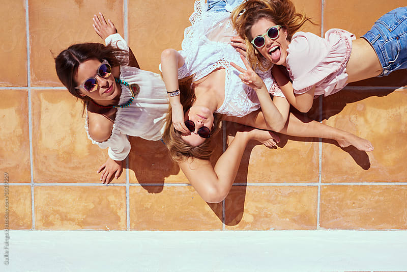 Three friends in sunglasses having fun on tiled floor outdoor by Guille Faingold for Stocksy United