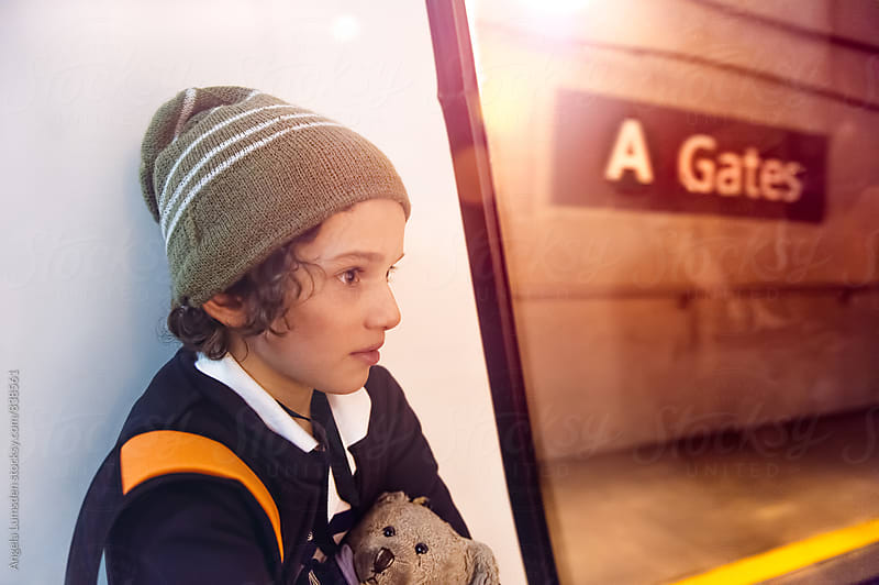 Boy traveling on an underground train with a backpack and a teddy bear by Angela Lumsden for Stocksy United