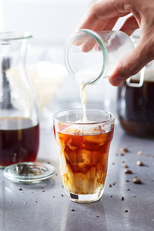 hand pouring milk in cold brew coffee by Martí Sans for Stocksy United