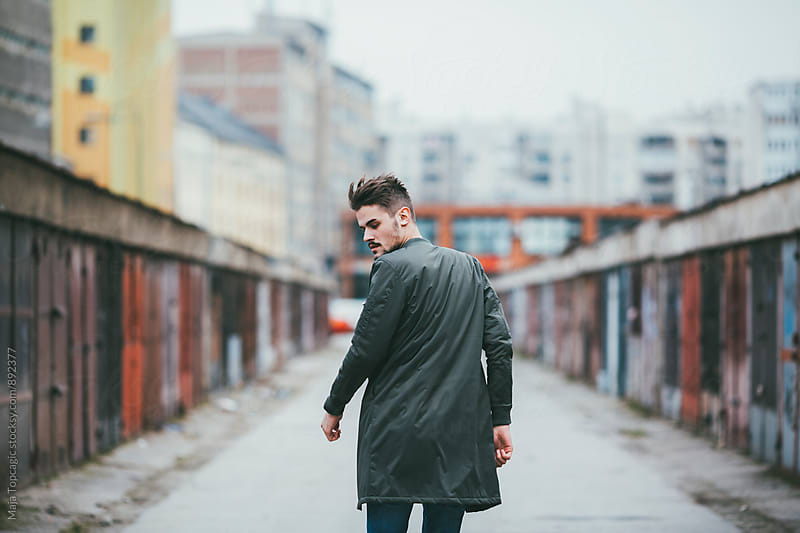 Young man walking in a neighbourhood by Maja Topcagic for Stocksy United