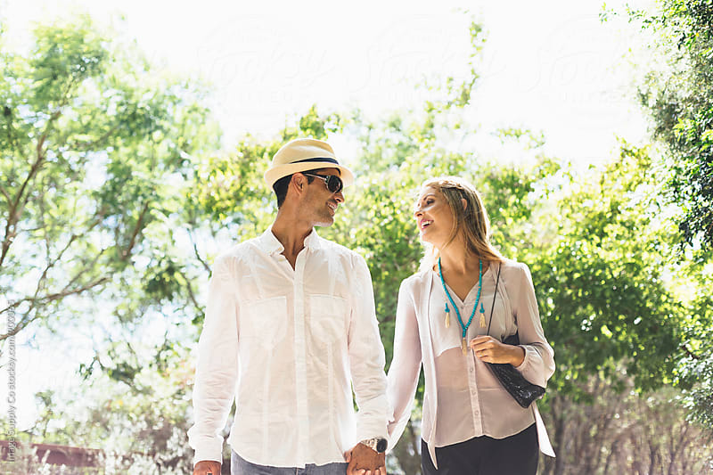 Young couple walking in park. by Image Supply Co for Stocksy United