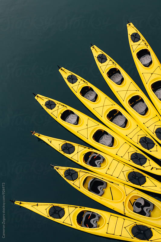 yellow sea kayaks tied together in water by Cameron Zegers for Stocksy United