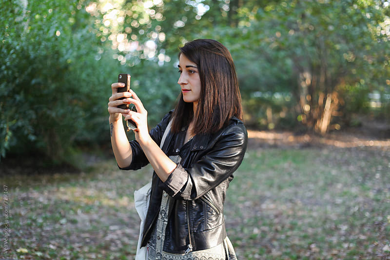 Woman using her mobile phone in the park  by Marija Mandic for Stocksy United
