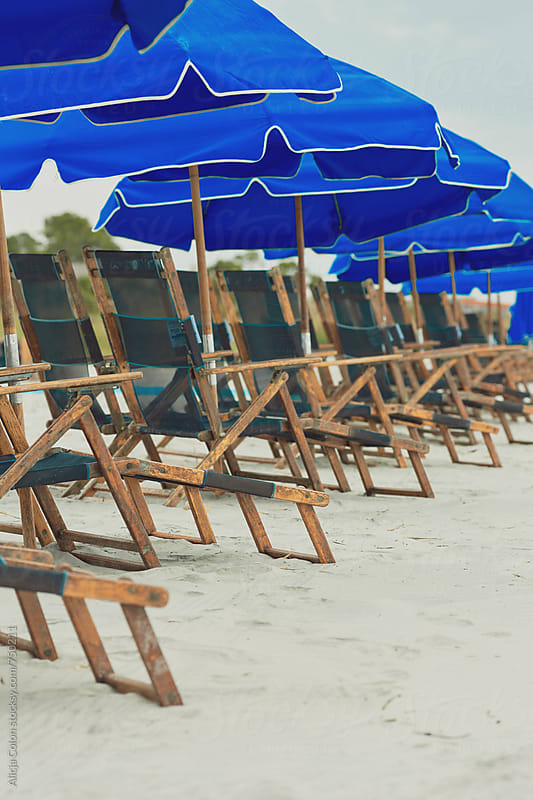 A line of chairs at the beach by Alicja Colon for Stocksy United