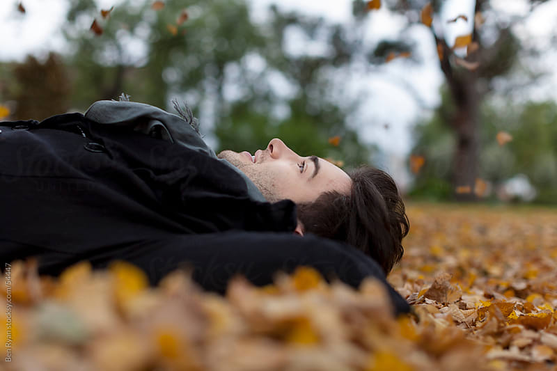 Stylish young latin male lying on his back in Autumn leaves by Ben Ryan for Stocksy United