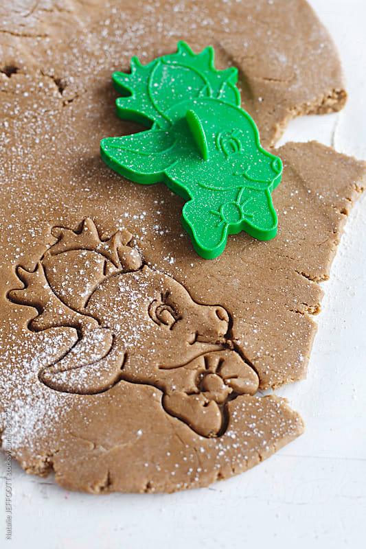 close up of rolled out gingerbread dough cut with reindeer shape by Natalie JEFFCOTT for Stocksy United