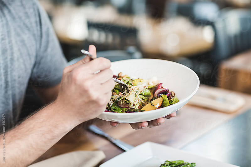 Closeup of man's hands eating fresh salad by Lior + Lone for Stocksy United