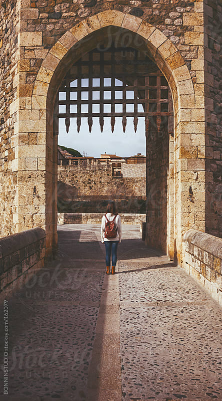 Back view of woman standing on the medieval bridge of Besalu. Girona, Spain. by BONNINSTUDIO for Stocksy United