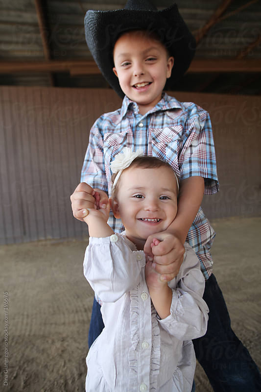 Big brother wearing cowboy hat holding hands with little sister by Dina Giangregorio for Stocksy United