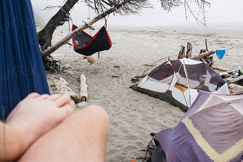 campsite with hammocks and tents on the beach in fog by Jesse Morrow for Stocksy United