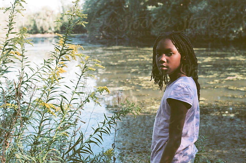 African American girl by a pond by Gabriel (Gabi) Bucataru for Stocksy United