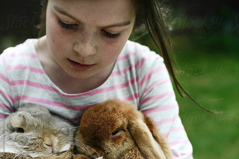 Girl holding two lop-eared rabbits by Kirstin Mckee for Stocksy United