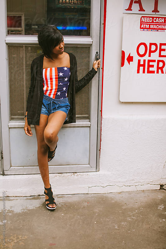 Black girl standing in front of door by Gabrielle Lutze for Stocksy United