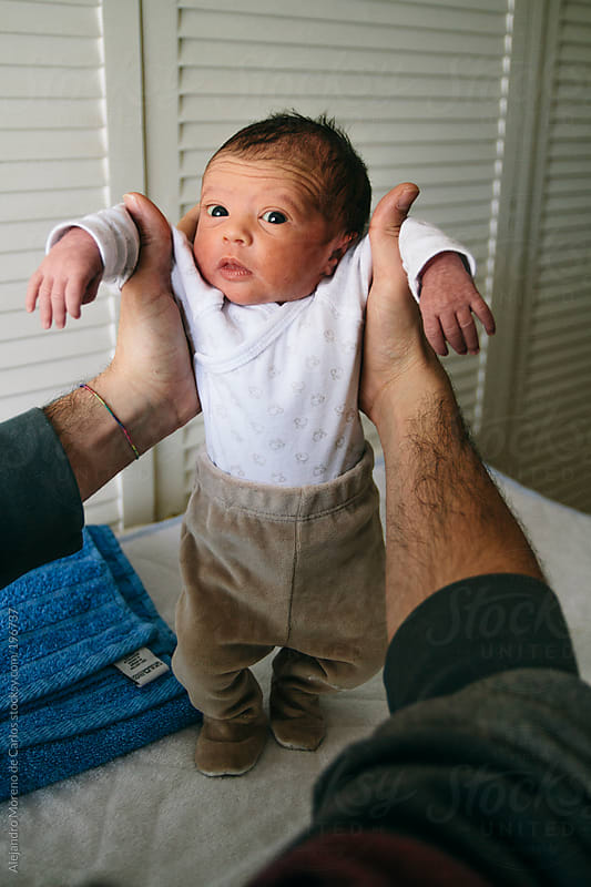 Newborn baby being held by his father by Alejandro Moreno de Carlos for Stocksy United