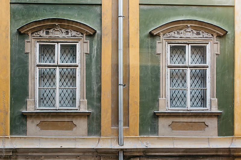Pair of windows on an old building in Timisoara, Romania by Gabriel (Gabi) Bucataru for Stocksy United